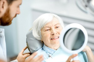 A dentist talking with an older woman who is looking at her new smile in the mirror while seated in a dentist's chair