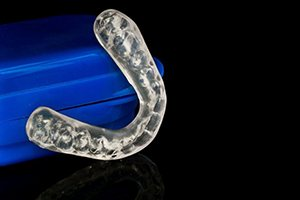 Invisalign clear aligner next to blue case